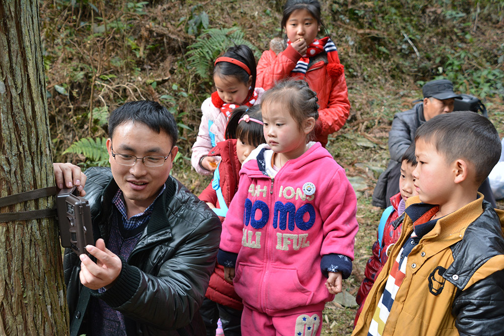 Fanjingshan nature reserve biologist Lei Shi showed children how to mount a camera trap on a tree. (Photo by Kefeng Niu)