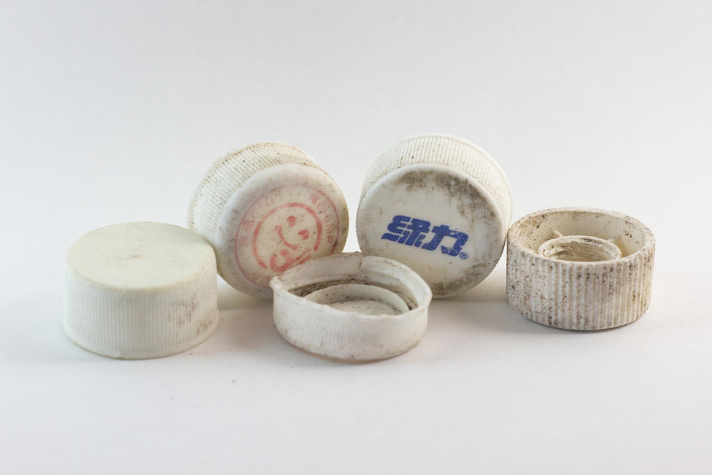 An assortment of plastic bottle caps from Midway Atoll. Sometimes, you can make out writing on the items that gives clues to their place of origin. Photo: Shannon Subers