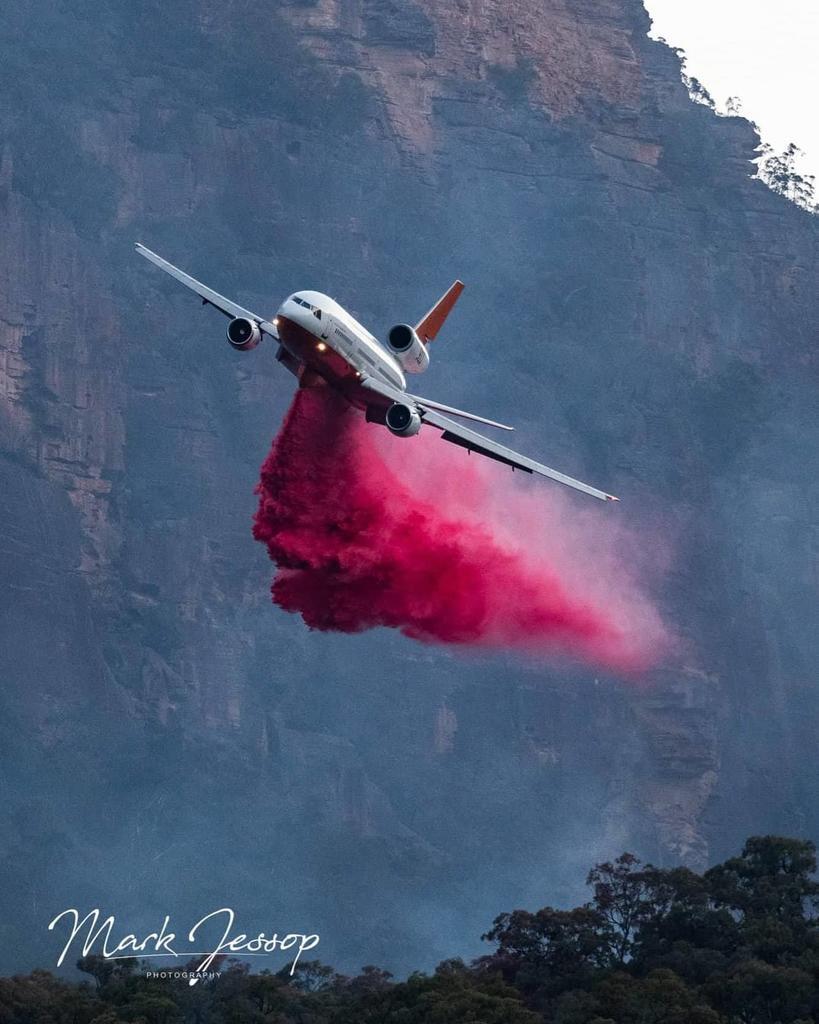 Plane dropping retardant on Gospers Fire.Picture: Mark Jessop