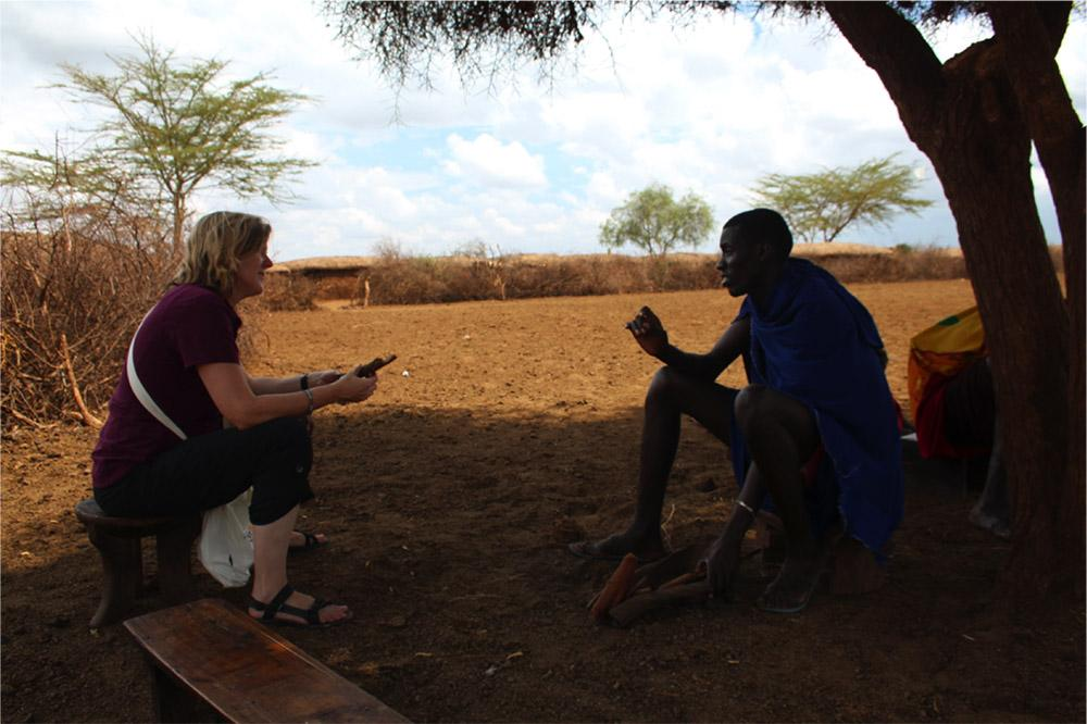 Christine Brown-Nunez, Ph.D., talks about wildlife interactions with a Maasai warrior just outside Amboseli National Park.