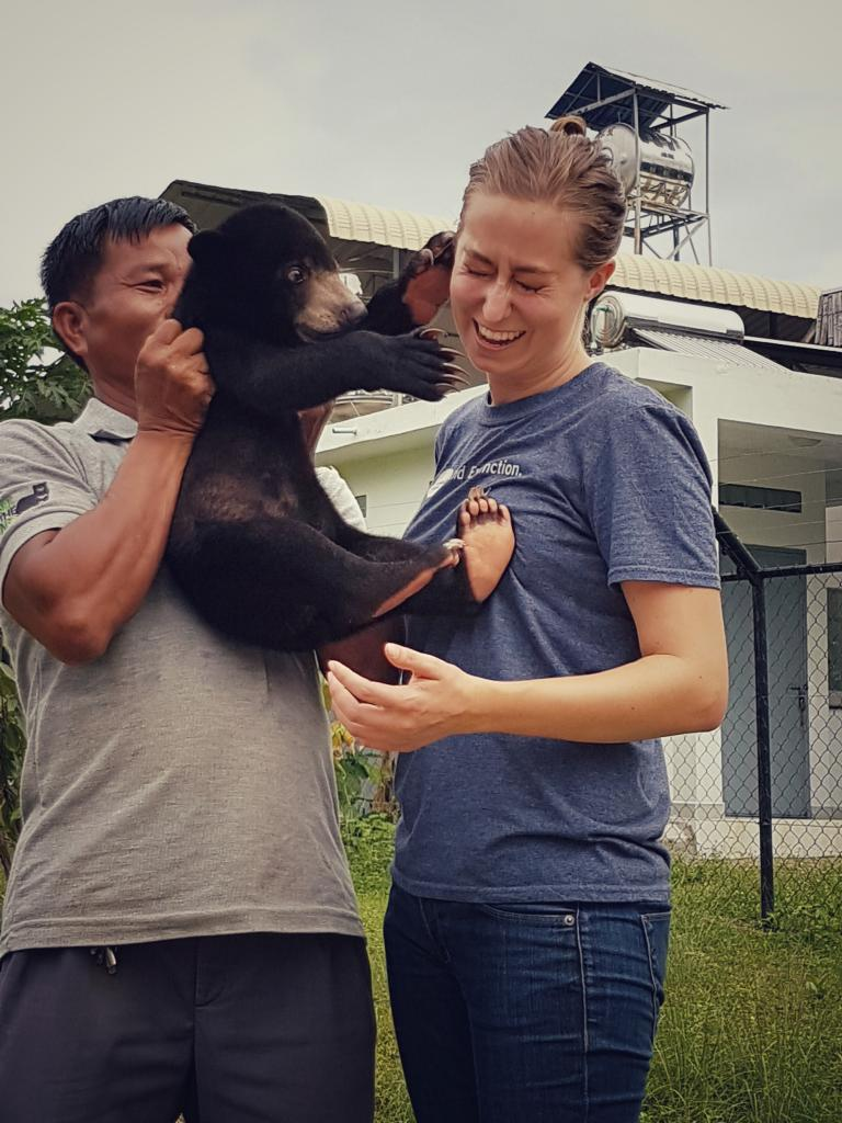 Community Engagement team member Elizabeth Davis receives some rough love from a rescued sun bear cub at the Free the Bears bear rescue center in Cambodia (picture: Elizabeth Davis, SDZG).