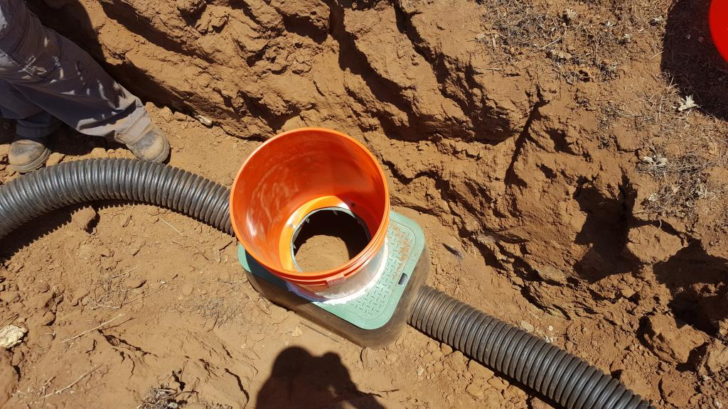 Figure 8. Two nested buckets, one attached to the top of the burrow chamber and one removable, allow us to access the burrow chamber.  Once finished, this trench will be filled in with dirt so the only thing you see is the very top of the bucket.