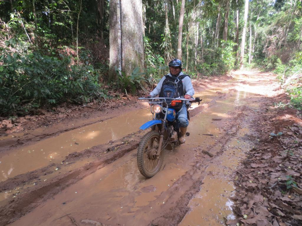 After days of rain roads turn into mud. Juan Racua navigates the motorcycle through some deep mud puddles.