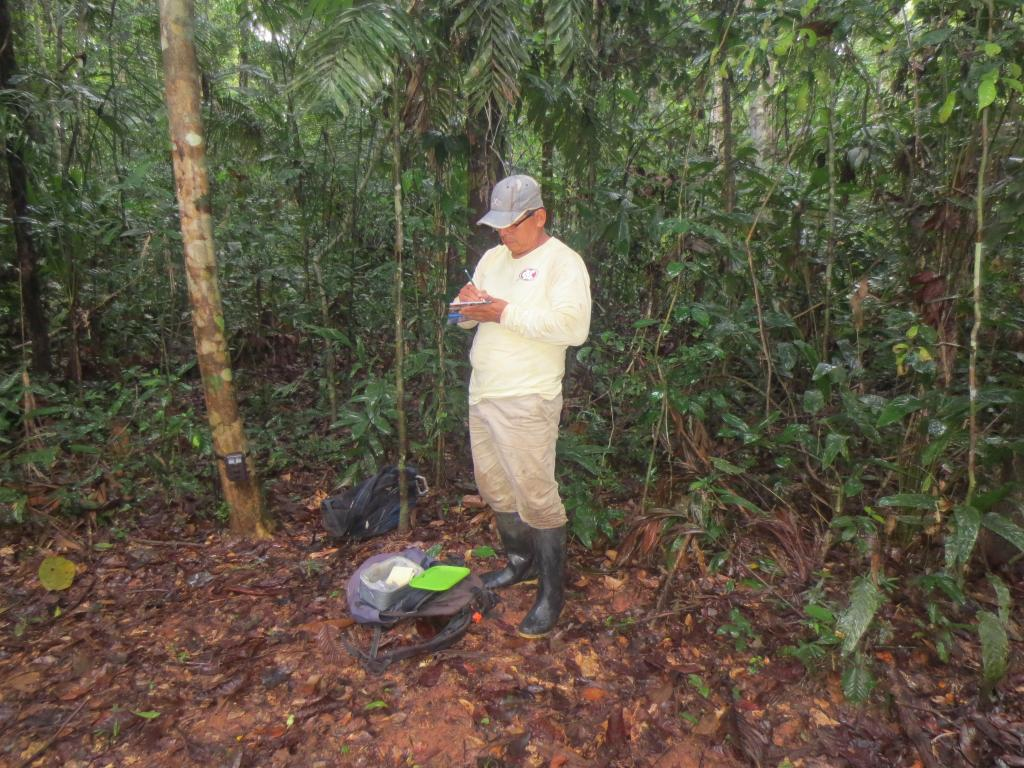 Ruben Aviana writes down all the information on the camera trap he just installed.