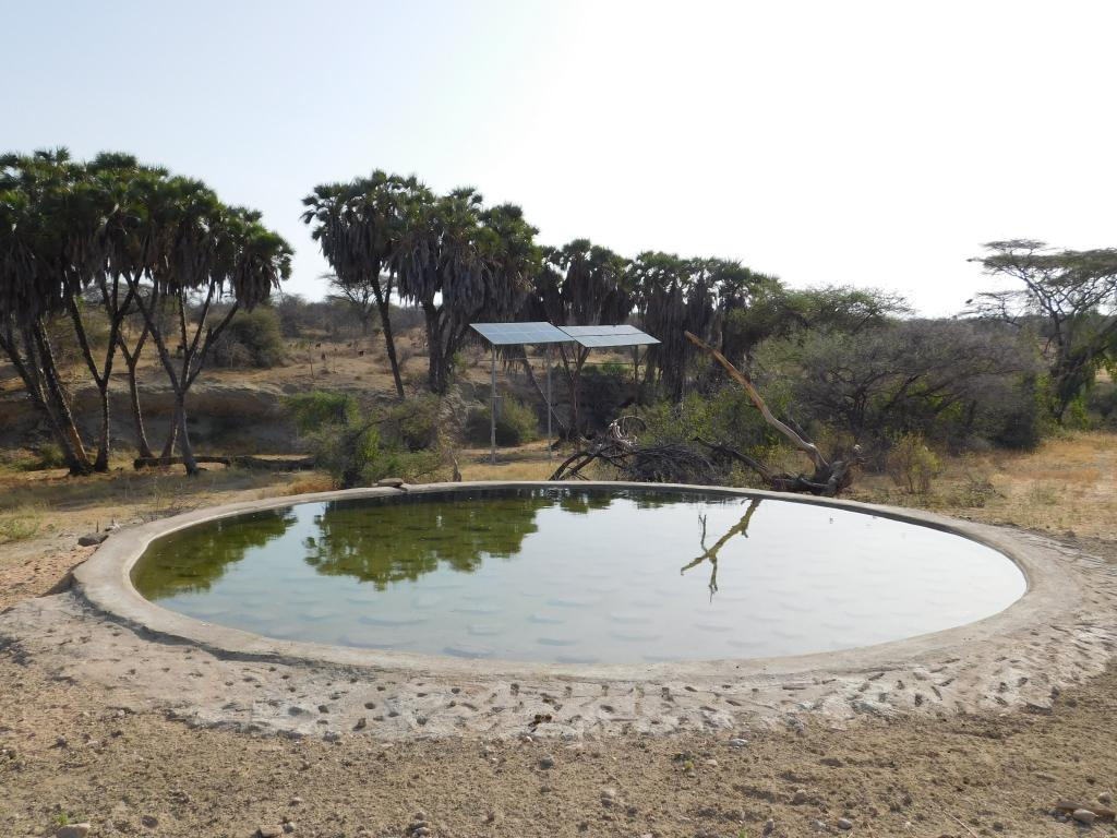A concrete waterhole with the two solar panels that power water to Lchorosowan behind.