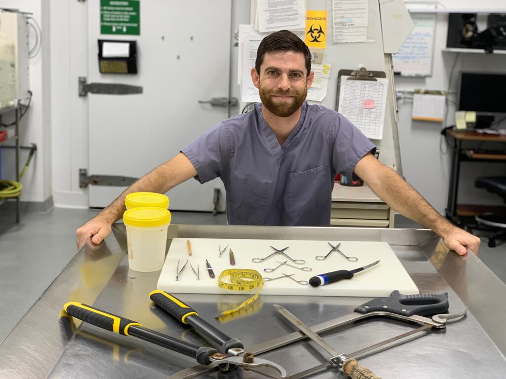 The author with necropsy instruments in the lab.